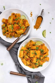 Two white bowls of Vegan Pumpkin Curry Pasta on a table with a dark grey napkin and two forks with wooden handles. There's also a scoop of yellow curry powder and lime garnishes on the side.