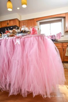 Decorate the food table at a princess elephant baby shower with a pink tulle…