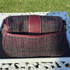 Fossil Purse Gently used Fossil Purse. Great little purse to add to your winter wardrobe. Gray and burgundy plaid with chain link and burgundy leather shoulder strap. Fossil Bags