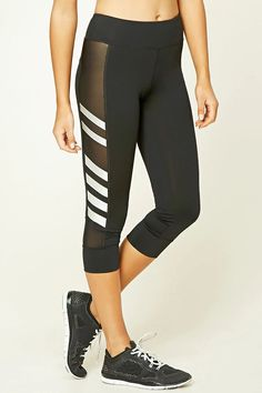 An athletic pair of knit capri leggings featuring mesh cutouts, reflective stripes along the sides, a hidden key pocket, and moisture management.