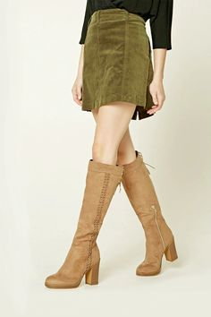 A pair of tall faux suede boots featuring a stacked heel, an interwoven trim down the side, a crisscross lace-up detail at the cuff, and a partial side zipper.