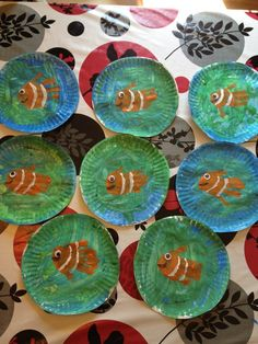 I had all of the children paint their large paper plates with blue and green. Once that dried, I painted their hands with orange paint and pressed their hand into the middle of their painted plate. Then we glued an eye Good for a multi-part art proj Diy Craft Projects, Diy Crafts For Kids, Projects To Try, Arts And Crafts, Under The Sea Crafts, Under The Sea Theme, Ocean Crafts, Fish Crafts, Painting For Kids