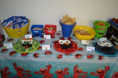 Sesame Street birthday party food. Broccoli Oscar, Strawberry Elmo, Blueberry Cookie Monster. The faces on the food containers are cake toppers from Amazon.