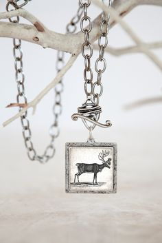 Vintage Reindeer & Wrapped Toggle Silver Plated Pendant | Collage from 1700's text and an 1800's black and white reindeer illustration. The reindeer is a universally recognized symbol of the holiday season. Reindeer also represent travel, strength, and endurance.
