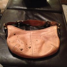 Authentic Coach leather purse Nude Coach leather purse with stud and rhinestone detailing.  The strap is gold and the zipper closure has a gold tassel.  Inside is pink with one zippered pocket Coach Bags