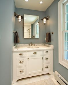 Olga Adler Interiors Fantastic blue bathroom design with blue walls paint color, white bathroom cabinet vanity with brushed nickel pulls, marble counter top, rectangular pivot mirror, chocolate brown towels and brushed nickel marine sconces. Rustic Wall Sconces, Bathroom Sconces, White Bathroom, Small Bathroom, Bathroom Lighting, Bathroom Wall, Master Bathroom, Master Baths, Downstairs Bathroom