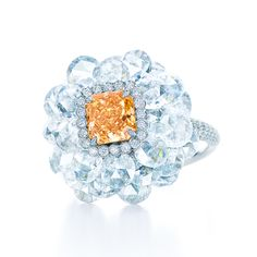 Flower ring in platinum with a 1.14-carat, rectangular modified brilliant Fancy Intense Yellow Orange diamond and rose-cut white diamonds. #TiffanyPinterest #TiffanyBlueBook