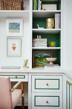 Amazing home office features a wall of built-in bookcases, with backs of bookcases painted emerald green, fitted with a built-in desk lined with pink vintage chair.