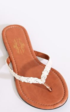 Faux leather thong sandal featuring faux leather straps with crochet trim. Rubber sole with traction bottom. Lined. Lightweight.Imported