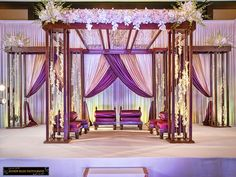 We liked the way this mandap looked (as discussed when we met) but would change the colors to be more ethnic (i.e. green, gold, cream, etc.)...and would be open to using less flowers on the top front but would like there to be some dangling as well as some pieces on the top of each pillar