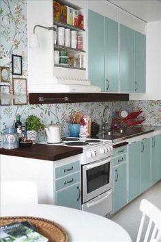 Painted cabinets and pretty wallpaper can completely transform a kitchen, giving it a stylish vs. utilitarian feel similar to other rooms in a house