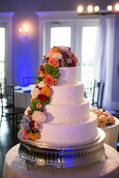 Four tiered round brides wedding cake with cascading vibrant colored fall flowers on silver cake stand - Photos by The Mamones