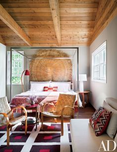 In a guest room, an Aboriginal fiber mat is displayed behind the Room & Board bed; the 1950s chairs are from Neo-Studio, and the rug is by Jonathan Adler.