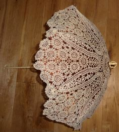 a 19th century folding parasol with an ivory handle. The cover is made of very fine Tatting forming a very attractive design over a bronze colour silk and lined in cream silk.