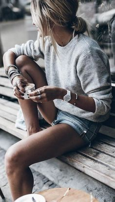 Grey sweater with faded denim shorts silver bracelets, white watch
