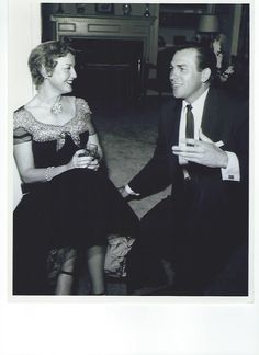 From an original negative: photo of Jeanette MacDonald and Howard Keel at Barbara Stanwyck's party. - ESCANO COLLECTION