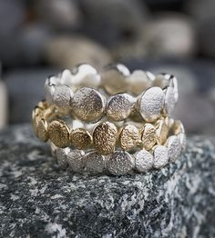 Reminiscent of the smooth rocks found on riverbanks, these nature-inspired pebble bands are carved into wax molds and cast in precious metal. Packaged in a set of three.