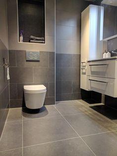 Wij hebben MEER dan 50 tinten grijs! Zoals deze leuke combinatie van donker en lichtgrijze tegels en kleine grijze mozaïek tegels in de nis boven de toilet. Prachtige moderne badkamer!
