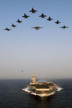 Aircraft from Carrier Air Wing (CVW) 7 fly over the Nimitz-class aircraft carrier USS Dwight D. Eisenhower (CVN 69).