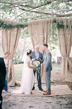 "This Gorg Australian Wedding Will Send You Eloping #refinery29  http://www.refinery29.com/100-layer-cake/1#slide-15  ""We were married under the most wonderful tree that had the perfect horizontal branch stretching out to one side. So, I bought some long lengths of Hessian to drape over the branch and just tied them at the base with twine to form an easy and dramatic backdrop to be married in front of. I hand-painted the word 'joy' on the middle one for us to be married under."""
