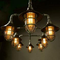 Die Glühbirnen bei diesem Kronleuchter werden durch Schutzkäfige im indutriellen Stil geschützt