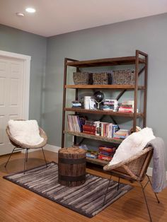 This charming reading nook features a rustic wood bookshelf, small round chairs and a tree stump ottoman. Furry white pillows add a sense of comfort, while a gray striped rug grounds the space.