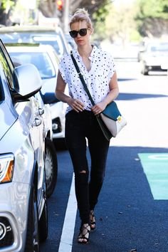 January Jones looks effortlessly chic in a pair of lightly distressed black jeans with a contrast top and laceup sandals.   - HarpersBAZAAR.com