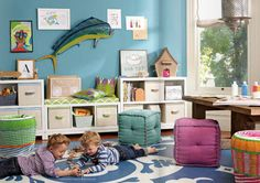 cozy playroom...love the poufs, colorful contrast wall and varying heights of book cases.