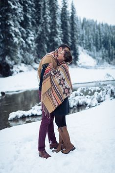 Romantic winter christmas engagement session in the foothills of the canadian rocky mountains. Love the tribal blanket how it stands out from the snow!