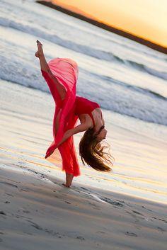 Flexible dancer stretches in red beach dress