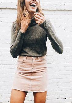 Olive sweater with blush denim mini skirt.