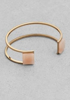 Graphic angles, polished gold-tone surface and genuine gemstones come together to form this airy and sophisticated cuff. Due to the nature of the stone, each piece has a unique appearance.