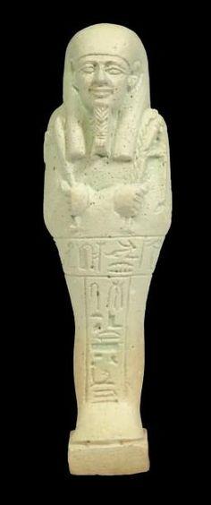 """OUSHEBTI AU NOM DU PRÊTRE OUNER ET SCRIBE DU TEMPLE DE PTAH NÉFERKA. Il est momiforme, coiffé de la perruque tripartite, paré de la barbe postiche, et tient les instruments aratoires. Les jambes sont gravées d'une inscription hiéroglyphique en T: """"Que soit illuminé l'Osiris le Prêtre ouner, le Scribe du temple de Ptah Néferka, né de Isetrechti juste de voix."""" Faïence siliceuse à glaçure vert clair. Égypte, Saqqara, Basse Époque, XXXe dynastie H_11,5 cm."""