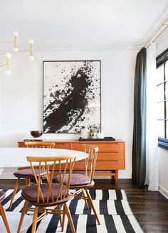 a black and white splatter artwork in a mid century modern dining space