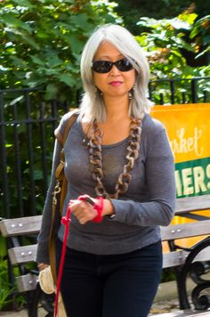 An example of a woman who makes her silver hair part of her general style, with silver/silvery jewelry and clothing in shades of black and gray.