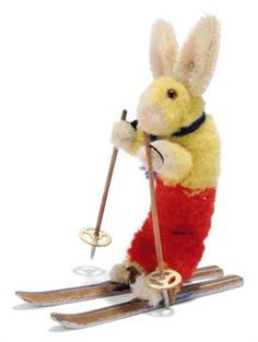 A STEIFF POM-POM SKI RABBIT, (Skihas 17), yellow, white and red wool, brown and black glass eyes, whiskers, mohair ears, blue knitted scarf, wooden skis and ski poles and FF button, 1936-1940 --5¼in. (13.5cm.) high