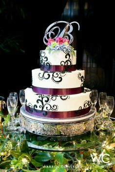 Purple ribbon wedding cake with black filigree and monogram topper