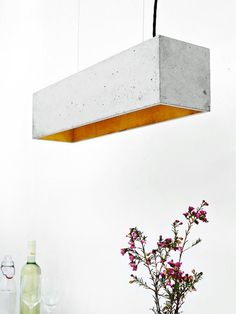 The rectangular pendant lamp is cast from a light gray concrete. It combines noble gold with rough concrete into a timeless and elegant designer lamp. The high quality gilding of the insides emits a pleasant warm light.
