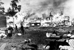 Russian men and women rescue their humble belongings from their burning homes, said to have been set on fire by the Russians, part of a scorched-earth policy, in a Leningrad suburb on October 21, 1941.