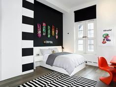 14 Inspirational Bedroom Ideas For Teenagers // Hanging graphic skateboards personalizes a space and can make a statement when brightly colored boards are contrasted against an all black wall.