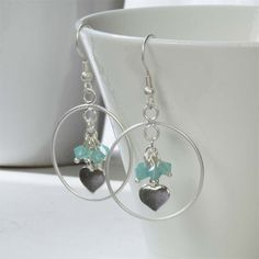Make a statement with these beautiful hoop earrings featuring a silver heart charm and aqua Swarovski crystal beads