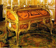 Oeben & Riesener, Bureau secrétaire de Louis XV.  Ce bureau est l'un des meubles les plus prestigieux jamais réalisés. Il demanda 9 ans de travail à l'ébéniste Oeben, puis à son élève Riesener. Son décor de marqueterie en bois précieux est complété par des bronzes dorés et des éléments en porcelaine de Sèvres. Le mobilier, au cours des XVII° et XVIII° siècles, est devenu un art de tout premier plan. Le travail du bois et le luxe et la finesse des décors témoignent du raffinement du style…