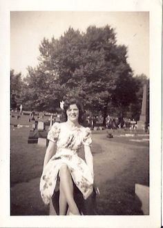 Woman looking very pretty...smack dab in the middle of a cemetery! What a funny place to get your pictures taken in.