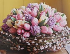 Tulips and hyacinths arranged in a pussy willow nest. Wouldn't this be lovely for a spring wedding centerpiece? Image via Sweet Romantic Not...