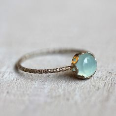 Aqua blue chalcedony gemstone ring. A brilliant and stunning rose cut blue chalcedony gemstone sits atop a patterned sterling silver band. Set is a scalloped sterling silver setting.  PLEASE NOTE THAT THIS RING IS VERY DELICATE! The color of the natural gemstone can vary some and the color can appear different depending on your screen. I do offer a free exchange if you aren't 100% satisfied with the ring's gemstone color. Just ask. :-)  The gem measures 6mm wide and the sterling silver…