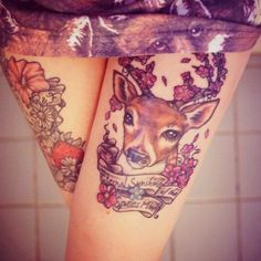 Flower tattoo on one thigh and a tattoo with a deer and some flowers on the other