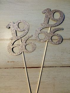 Celebrate your class reunion in style! These graduation year sticks are perfect for centerpieces, cake toppers or photo props! Each class year measures approx 3.5 wide and 4 tall. Once attached to stick they are approx 11 tall. Made of your choice of glitter cardstock! Available Colors: Gold, Silver, Black, Red, Orange, Green, Pink, Purple, White, Purple, Brown, Yellow, Blue.  Please message for custom color requests! Mix and match colors to match your school colors! Be sure to include color…