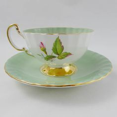 Gorgeous green tea cup and saucer made by Aynsley. Oban shape, with large pink cabbage roses on the inside and outside of the tea cup. Cup and saucer are green. Gold trimming on cup and saucer edges, and gold handle and foot of tea cup. Excellent condition (see last photo). Markings read: