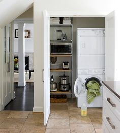 A stackable front-loading washer and dryer combo fits easily into a wide closet, leaving ample space for a freestanding shelving unit to corral linens and kitchenware. This closet's location near the kitchen makes multitasking while cooking or cleaning easy. Tiny Laundry Rooms, Laundry Room Shelves, Laundry Tips, Mud Rooms, Kitchen Remodel, Storage Closets, Storage Room, Stackable Washer And Dryer, Stacked Washer Dryer