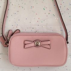 "Coach pink leather mini  crossbody handbag NWT Pink leather double zip mini handbag adorned with a pink bow, 1 pocket and  2 cardslots on interior, silver tone hardware. Approx measurements: 6.5x3.75x1.5 with an adjustable 25"" strap drop. PhOto 2 truest color. PRICE FIRM Coach Bags Crossbody Bags"